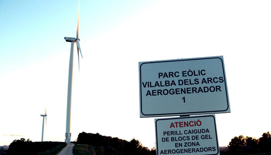Un cartell senyalitzant un parc eòlic a Vilalba dels Arcs, a la Terra Alta, amb dos aerogeneradors al fons.