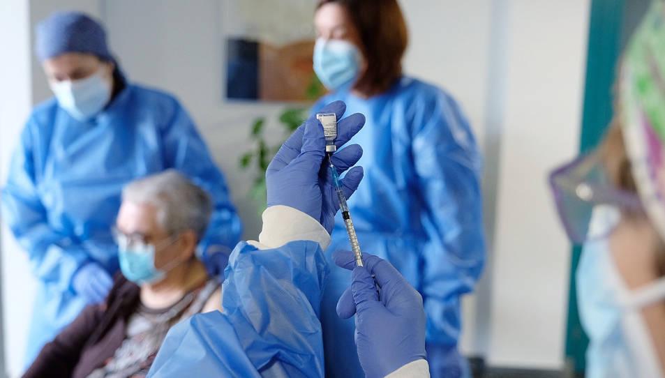 Un sanitàira treu una dosi del vial de la vacuna.