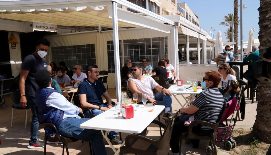 Un grup de persones assegudes en una terrassa d'un bar del passeig marítim de Coma-ruga, al Vendrell, aquest Divendres Sant.