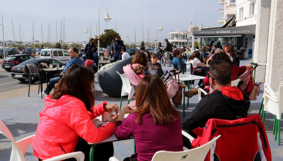 Persones consumint en una terrassa d'un bar de la zona marítima de l'Ampolla aquesta Setmana Santa.