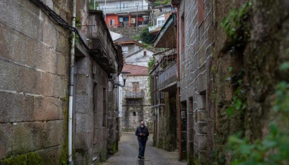 Un home camina pels carrers de Beade.