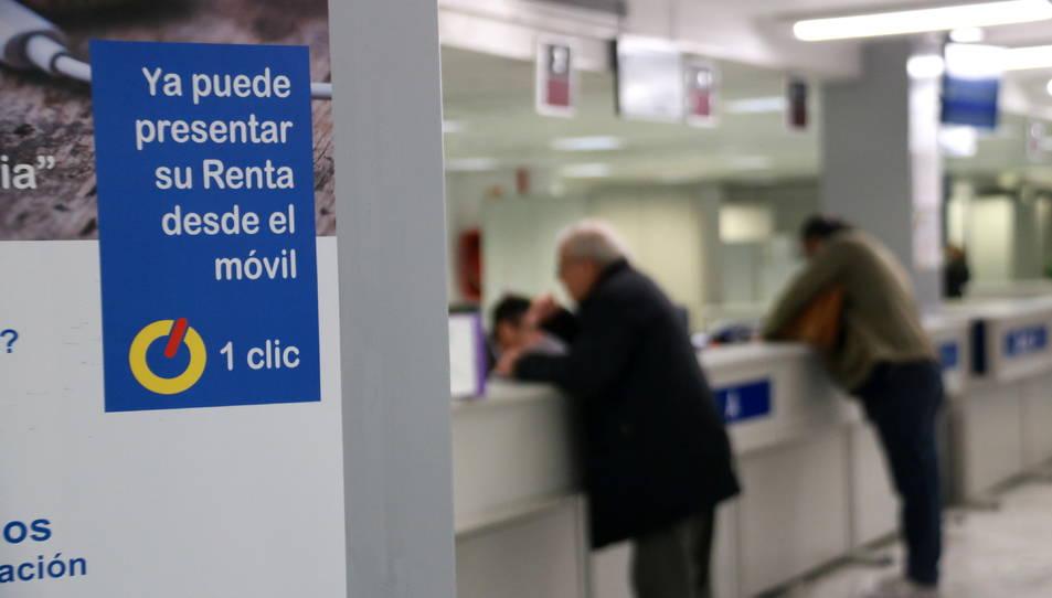 Un cartell a la seu de l'Agència Tributària a Catalunya amb indicacions sobre la presentació de la declaració de la renda i amb contribuents fent consultes de fons,