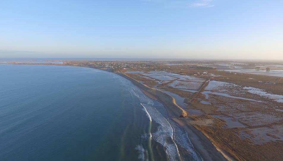 Pla aeri de la platja de la bassa de l'Arena, amb el cordó dunar interromput en alguns punts i la urbanització de Riumar al fons.