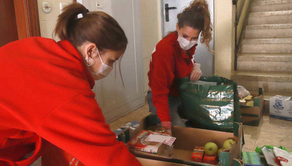 Dues tècniques de Creu Roja Tarragona posant el menjar en bosses de plàstic a casa d'un beneficiari.