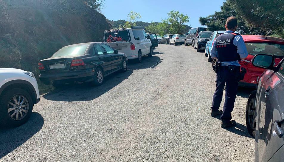 Un mosso davant fileres de cotxes mal aparcats en vorals de la carretera durant les vacances de Setmana Santa a Tarragona.