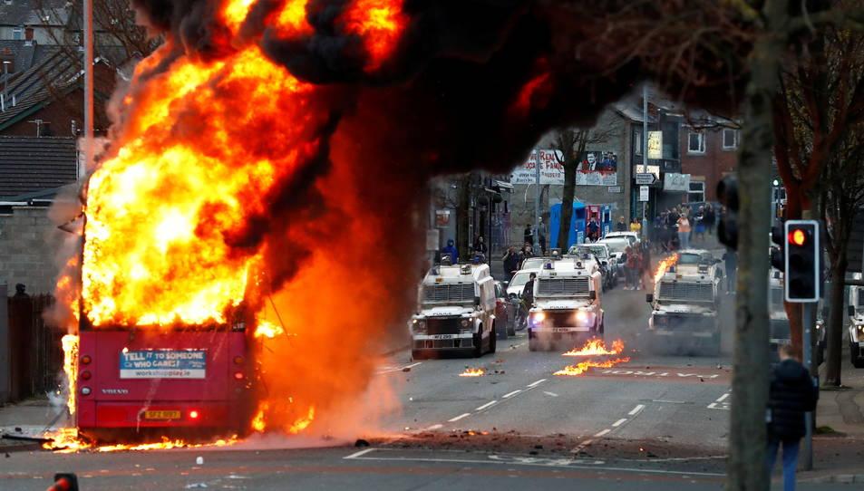 Vehicles policials darrere d'un autobús en flames a Shankill Road durant les protestes a Belfast.