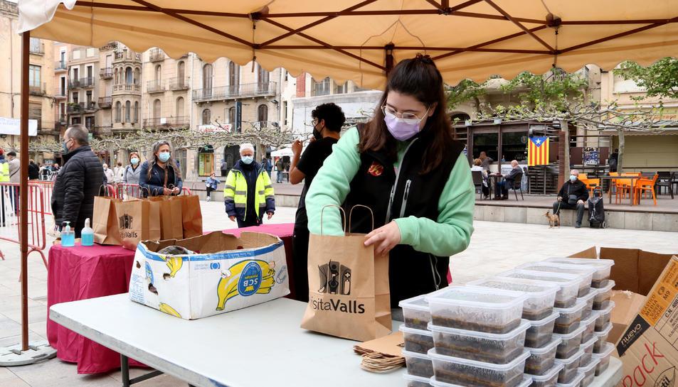 Una noia preparant racions de faves a la plaça del Pati de Valls, un dels punts habilitats de recollida de la 3a edició de la Favatada.