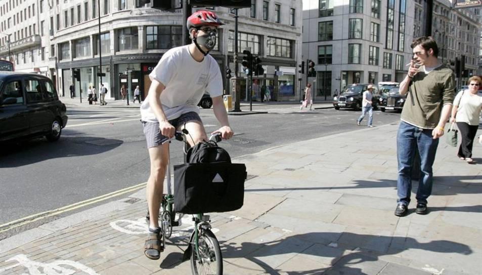 Un londinenc es dirigeix a treballar amb bicicleta amb mascareta a la cara a Londres.