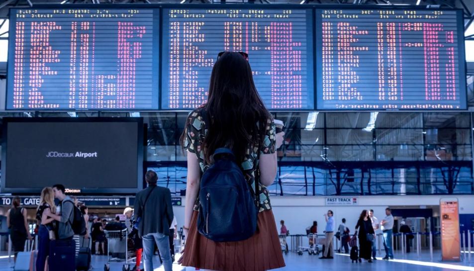 Una noia espera el seu vol en un aeroport.