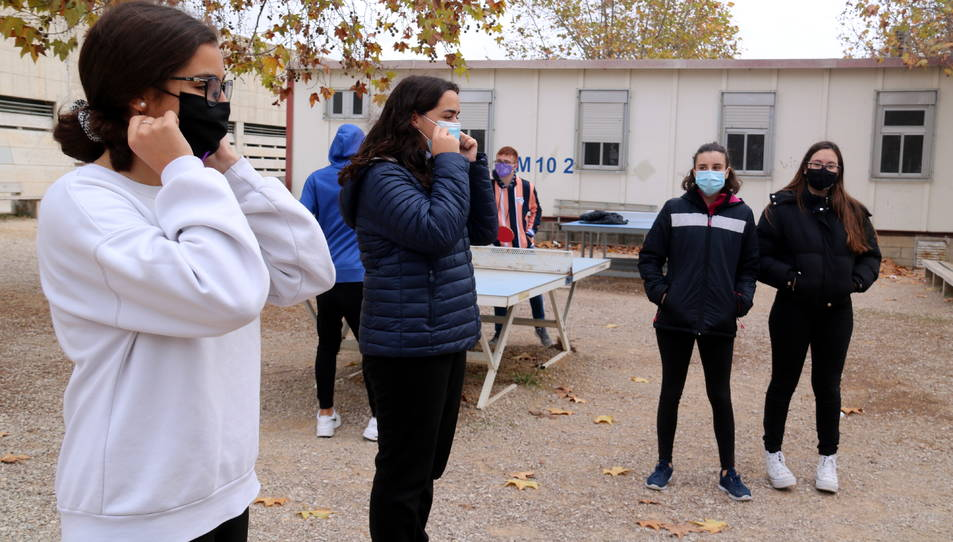 Dues alumnes de l'Institut d'Alcanar explicant els bons usos de la mascareta als seus companys.