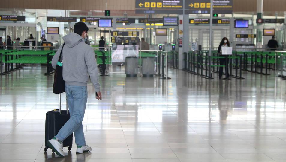 Un passatger a la zona d'arribades de la T1 de l'aeroport del Prat