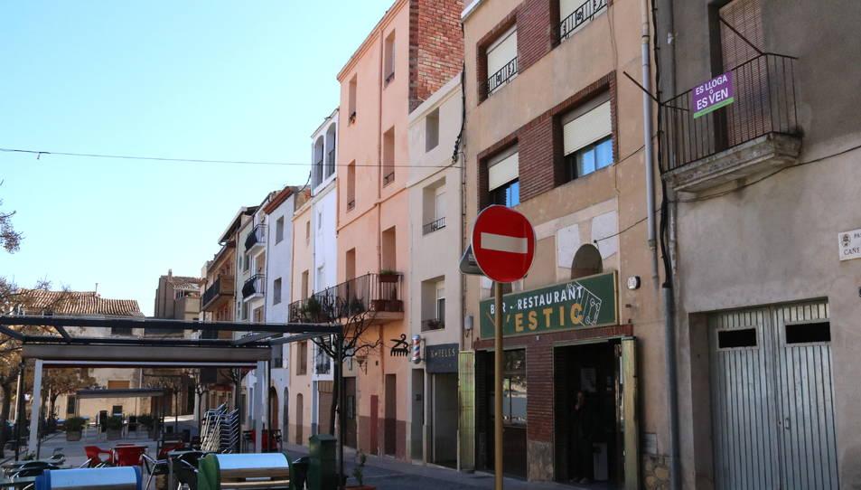 Una casa amb un cartell de lloguer i/o venda, a la dreta de la imatge, en una cèntrica plaça de l'Espluga de Francolí.