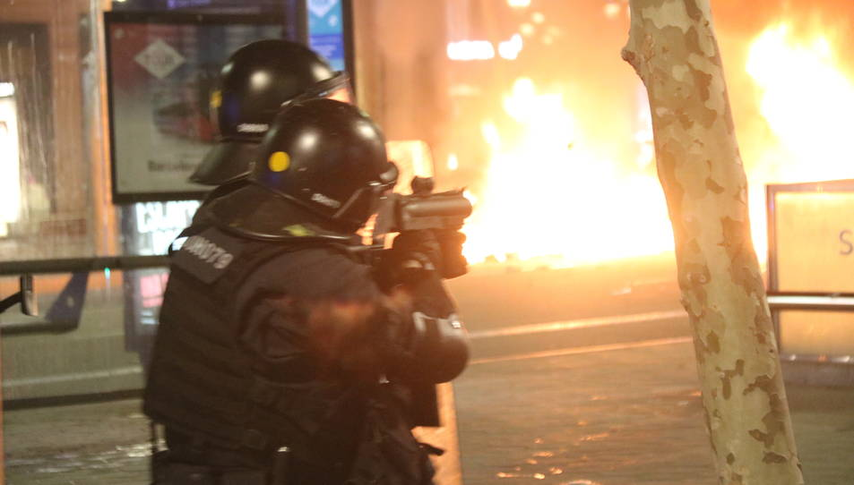 Un agent dels Mossos d'Esquadra dispara una bala de foam en el marc dels aldarulls per l'empresonament del cantant Pablo Hase.