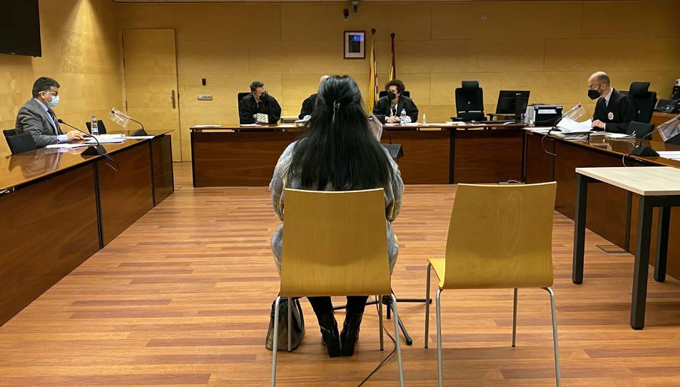D'esquenes, la cuidadora acusada d'estafar una veïna de Girona. Foto del judici a l'Audiència de Girona.