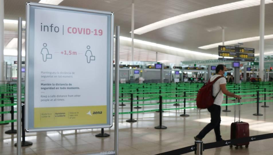 Un passatger arrossegant una maleta amb el control de seguretat de la T1 de l'Aeroport del Prat.