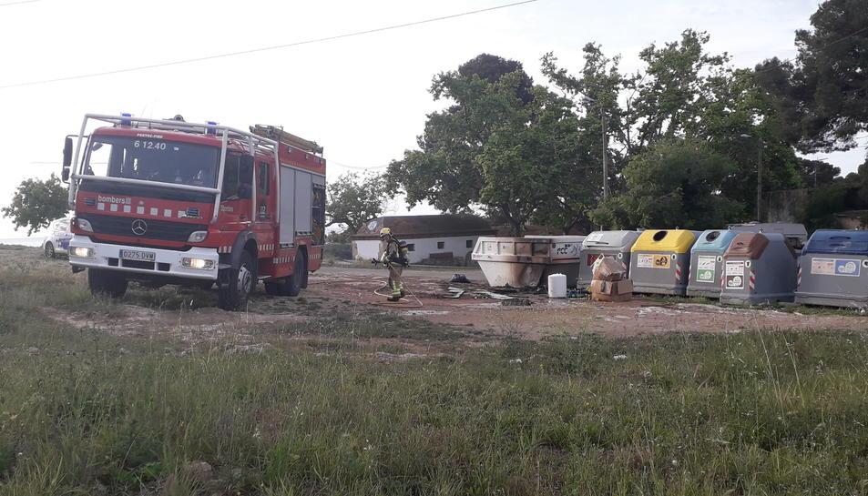 Els bombers remullant els contenidors que van cremar ahir a primera hora del matí.