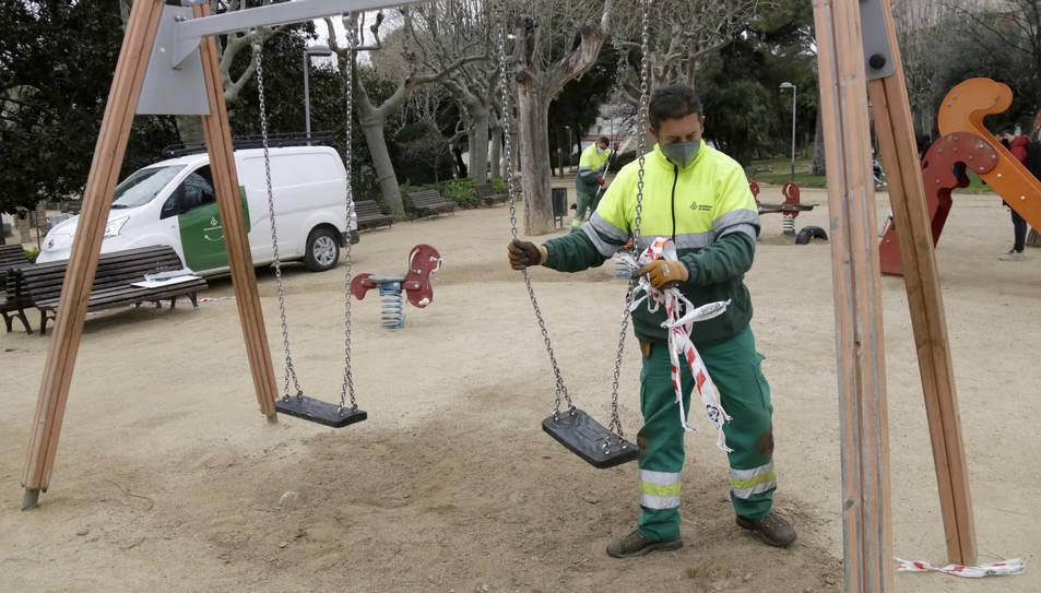 Operaris municipals de l'Ajuntament de Mataró desprecinten un parc infanti.