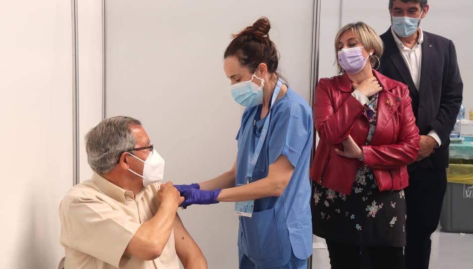 La consellera de Salut, Alba Vergés, mirant com administren una vacuna a un home al punt de vacunació massiva del Palau d'Esports Catalunya de Tarragona.