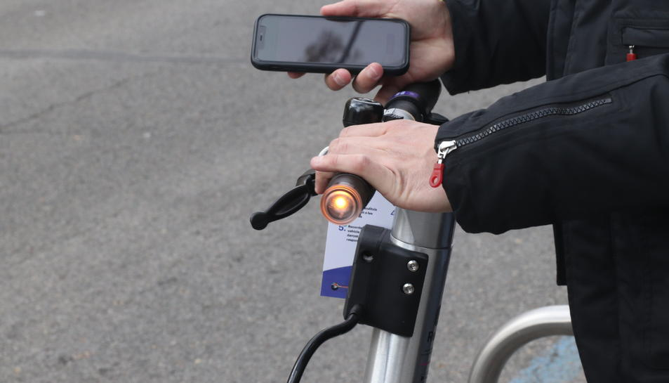 Imatge d'arxiu d'una pesona llogant un patinet elèctric amb el mòbil.