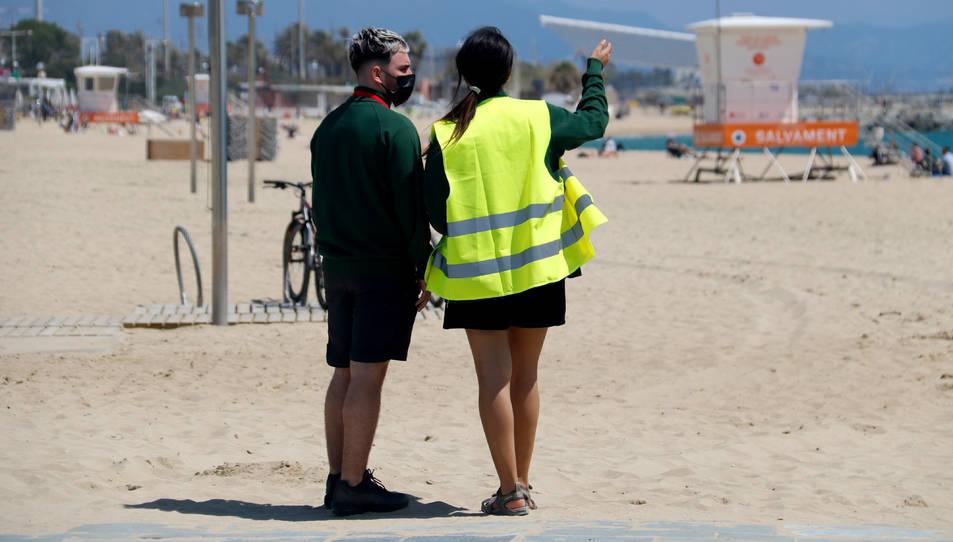 Dos informadors municipals, d'esquenes, a la platja del Bogatell