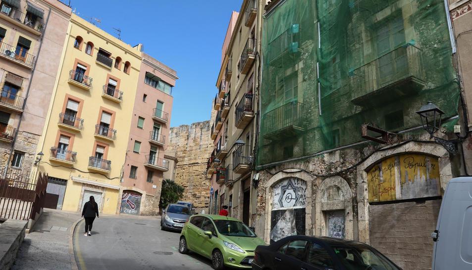 Una xarxa cobreix l'edifici del número 21 de la Baixada de la Peixateria, tapiat des de fa anys.