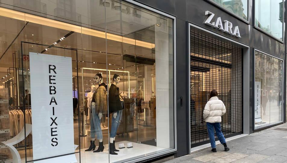 Una compradora davant d'una botiga Zara tancada al Portal de l'Àngel de Barcelona.