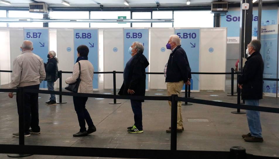 Diverses persones esperen el seu torn per rebre la primera dosi de la vacuna al punt habilitat a Fira de Barcelona.
