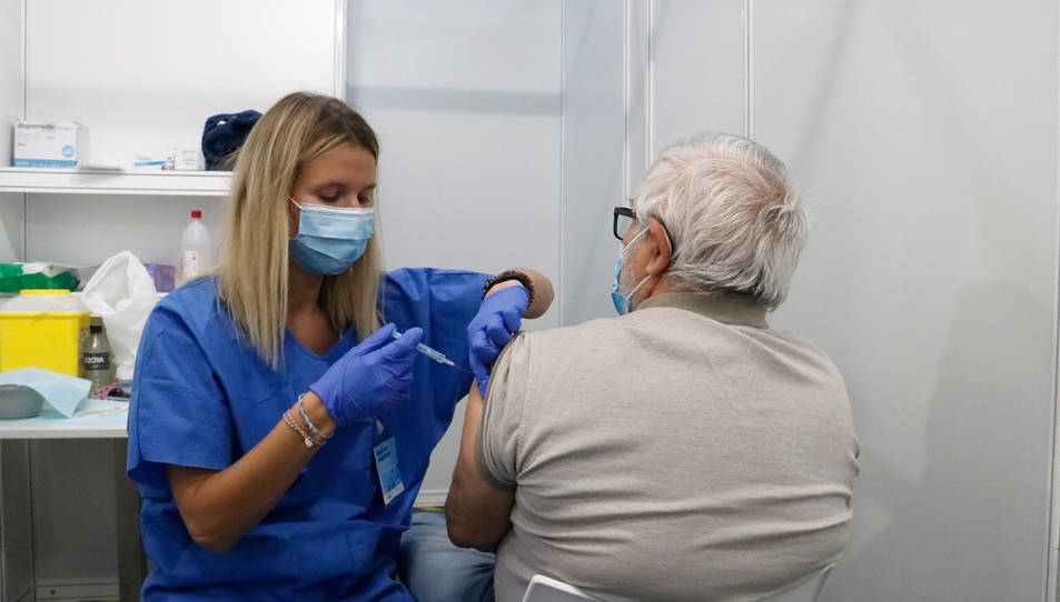 Una infermera vacuna un home en un dels box del punt de vacunació massiva habilitat a Fira de Barcelona.