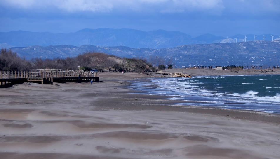 Tram nord de la platja de Riumar, amb l'aigua del mar apropant-se a les passarel·les de fusta.