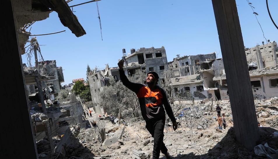 Pla general d'un palestí caminant sobre runes després de l'atac aeri i terrestre de l'exèrcit israelià a la Franja de Gaza.
