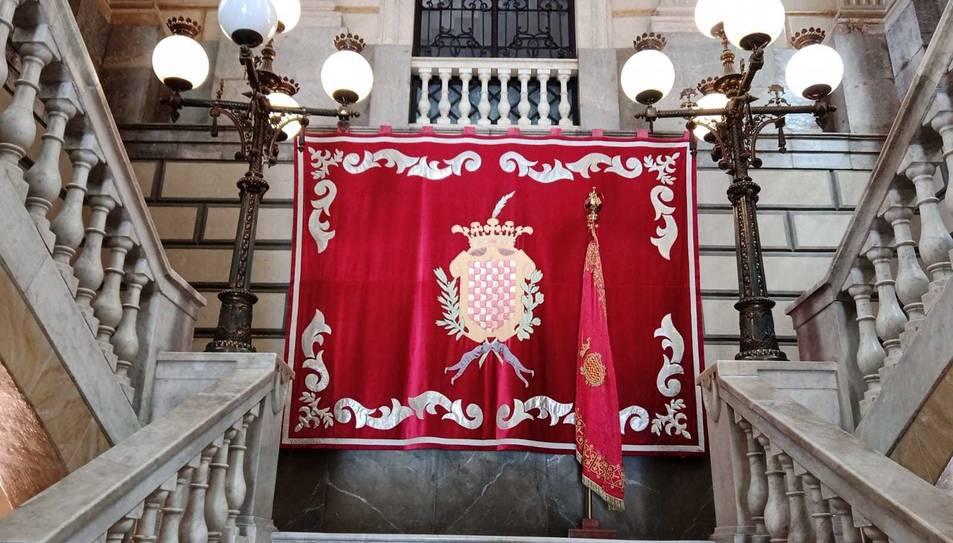 El domàs i la bandera de la ciutat presideixen les escales principals de l'Ajuntament de Tarragona.