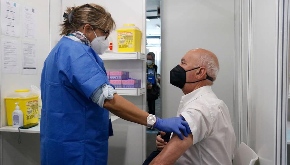 Una infermera parla amb un home just després que rebi la vacuna al punt habilitat a Fira de Barcelona.