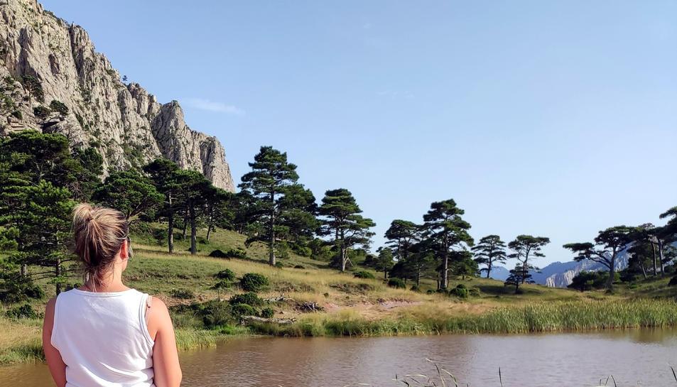 Pla mitjà d'una noia contemplant la Bassa de la Refoia al Parc Natural dels Ports.