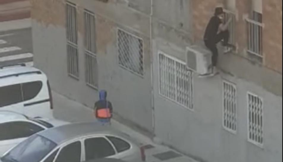 Imatge d'un dels joves grimpant per entrar a l'habitatge.