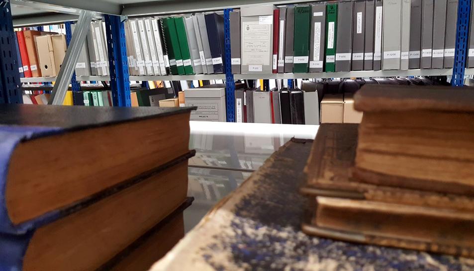 Primer pla de llibres i documents guardats en estanteries a l'arxiu general de la Diputació de Tarragona.