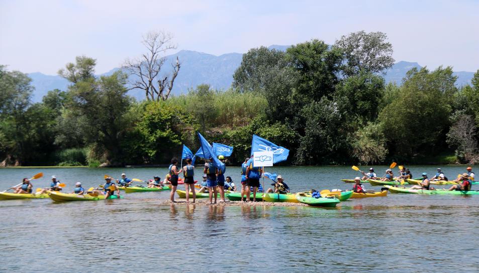 Els participants en la 20a Piraguada en Defensa de l'Ebre a la seva arribada a Tortosa, rodejant els activistes que han fet l'acció reivindicativa.