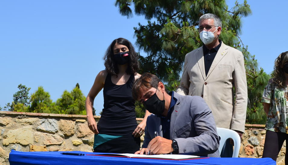 Dídac Nadal (Junts) signa el pacte d'entrada al govern municipal mentre s'ho miren Eva Miguel (CUP) i Pau Ricomà (ERC).