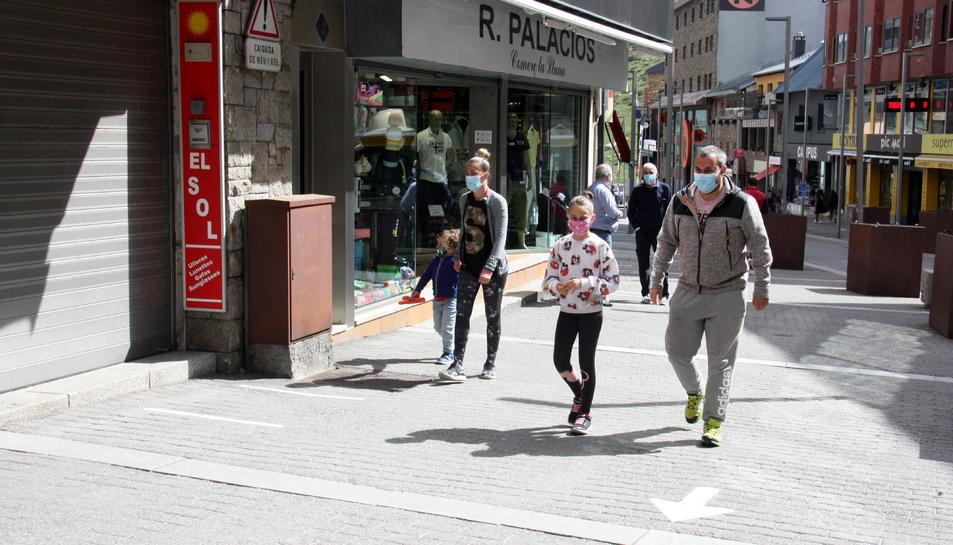 Un grup de persones passejant per un dels carrers comercials del Pas de la Casa.
