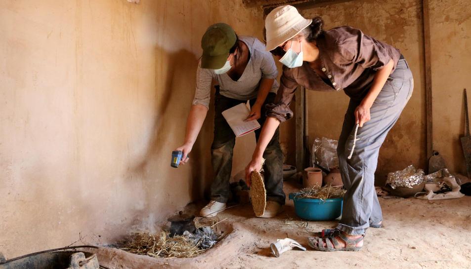 Pla obert de dues investigadores de l'ICAC analitzant una llar de foc recreada.