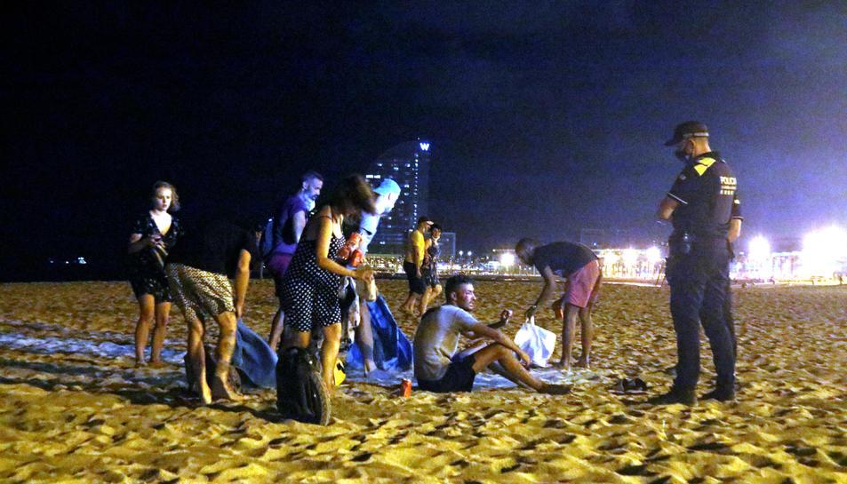 Un grup de persones que feia el 'botellón' a la platja de la Barceloneta de Barcelona s'aixequen davant la presència d'una línia d'agents de la Guàrdia Urbana abans de marxar, a quarts d'una de la matinada.