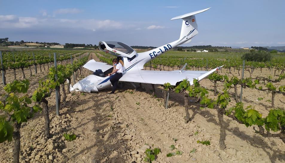 Pla general de l'avioneta del CESDA i del pilot parlant per telèfon damunt d'una ala.