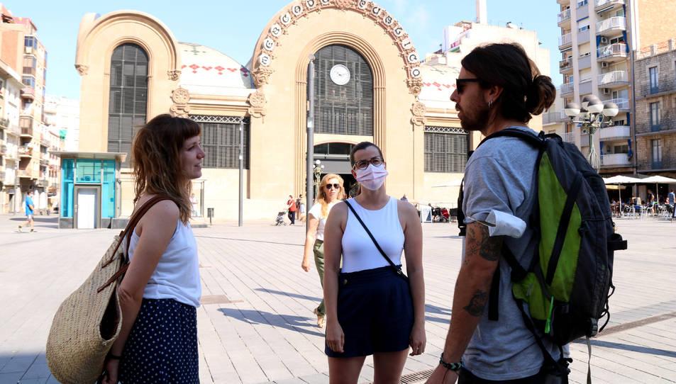 Tres joves, dos d'elles sense mascaretes, xerrant a la plaça Corsini de Tarragona, en el primer dia sense obligatorietat de dur mascaretes.