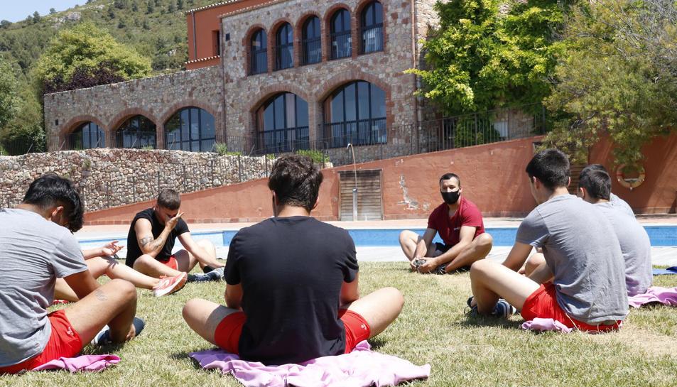 Uns menors fent estiraments als jardins d'un centre terapèutic per a adolescents, del grup Amalgama7, ubicat a l'Alt Camp.