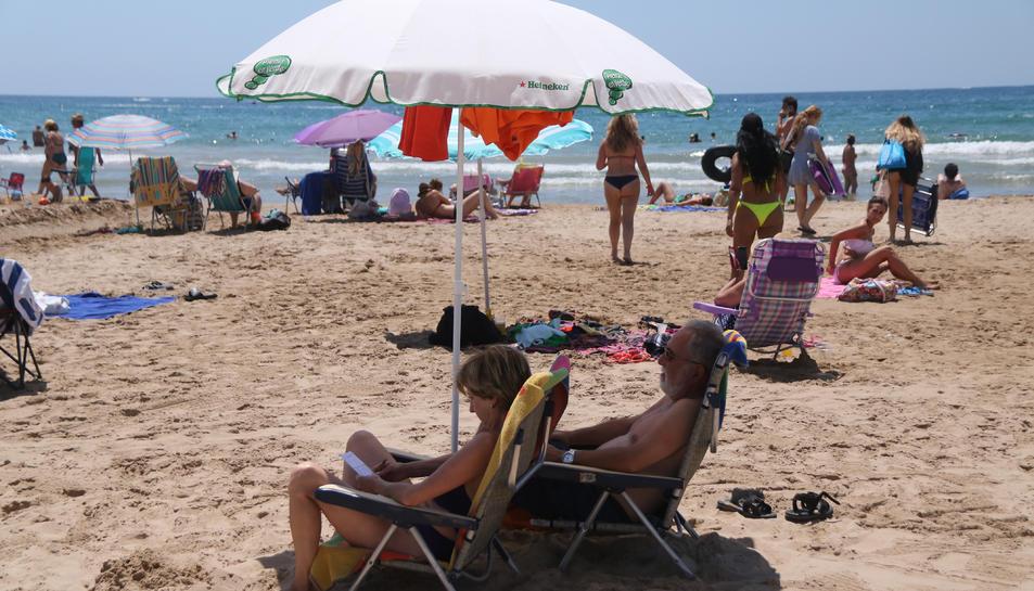 Pla mig de dues persones sota un para-sol a la platja de Salou.
