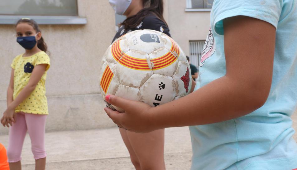 Pla detall d'una pilota a les mans d'una nena participant al casal d'estiu de la Fundació Pere Tarrés a Torredembarra.