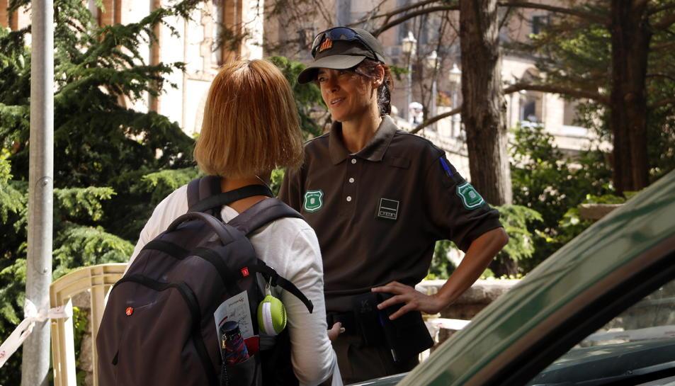 Una agent dels Agents Rurals explica a una turista que no pot accedir pel Camí de Sant Miquel.