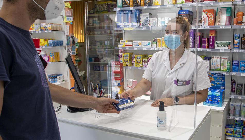 Una farmacèutica de la farmàcia Salazar, al carrer Cos del Bou, entrega un test d'antígens a un client.