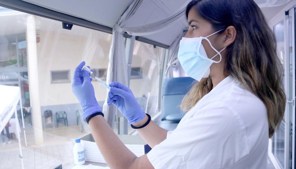 Una infermera preparant una dosi de la vacuna Janssen a l'interior del bus del Banc de Sang a Alcanar.