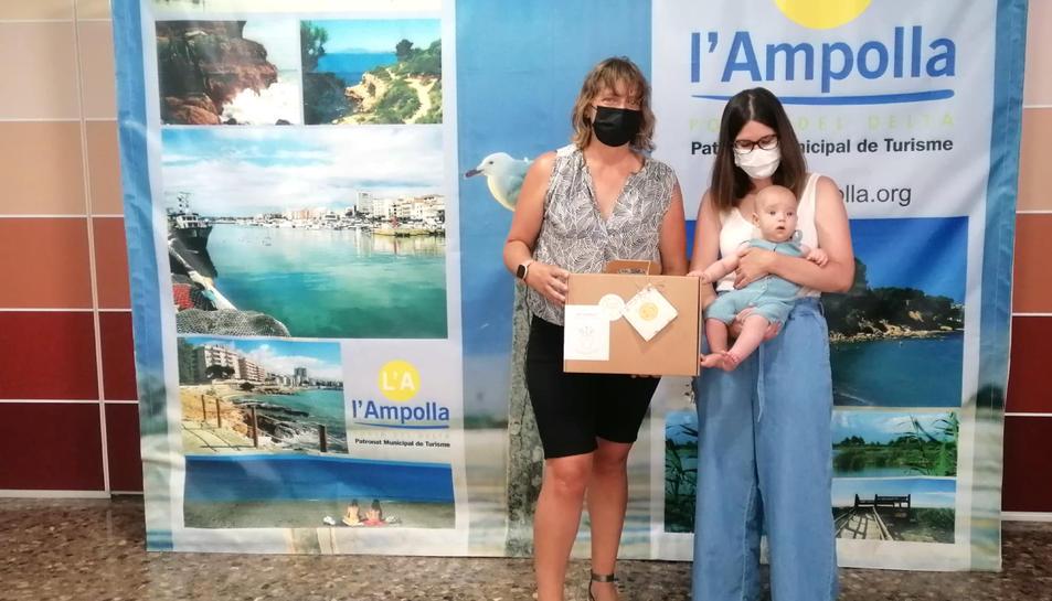 La regidora de Medi Ambient de l'Ampolla, Meritxell Faiges, fent entrega del lot de productes ecològics a una mare i el seu nadó.