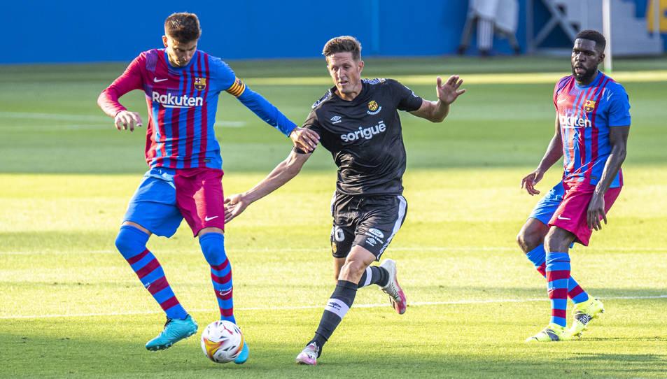 Gerard Piqué intenta aturar a Edgar Hernández durant el Barça-Nàstic.
